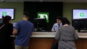 Движение людей line up для ждать обслуживания внутри банка TD сток-видео