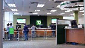 Движение людей line up ждущ обслуживание внутри банка TD сток-видео