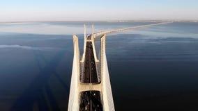 Движение на мосте Gama Vasco da над Тахо на заходе солнца в Лиссабоне, Португалии, виде с воздуха стоковое изображение