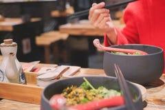 Движение нерезкости красных палочек владением руки женщин рубашки ест лапшу Стоковое Изображение RF