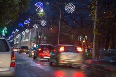 Движение ночи, автомобили на дороге шоссе на ноче в занятом городе, городском взгляде вечера захода солнца Рождество в городке Стоковая Фотография RF