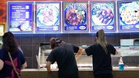 Движение окна дисплея чистки еды и работника людей покупая на фуд-корт сток-видео
