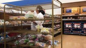 Движение работника запасая хлеб на стеллаже для выставки товаров