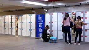 Движение регулярных пассажиров пригородных поездов кладя их багаж внутри шкафчика