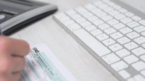Движение слайдера крупного плана налоговой формы 1040 завалки женщины на столе рядом с клавиатурой и калькулятором компьютера вид сток-видео