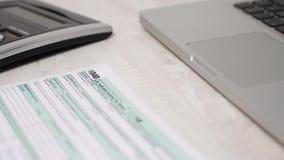 Движение слайдера снятое налоговой формы 1040 на столе рядом с ноутбуком и калькулятором компьютера видео 4K акции видеоматериалы