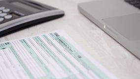 Движение слайдера снятое налоговой формы 1040 на столе рядом с ноутбуком и калькулятором компьютера видео 4K видеоматериал