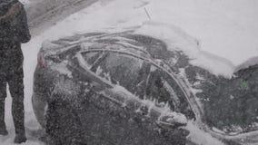 Движение снега и льда людей очищая с ее окна ветровой защиты автомобиля сток-видео