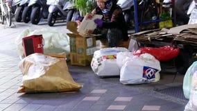 Движение старухи рециркулируя картон и бутылку на дороге города