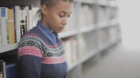 Движение тележки молодой Афро-американской женщины книга чтения сидя на поле в университетской библиотеке сток-видео