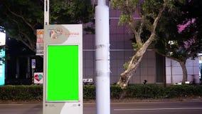 Движение транспортного потока во время на ночи с зеленой доской движения экрана