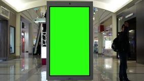 Движение ходить по магазинам людей и зеленая афиши экрана в середине сток-видео