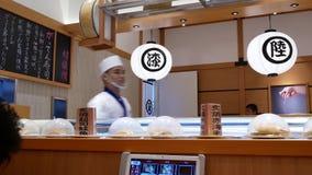 Движение шеф-повара подготавливает суши около конвейерной ленты внутри японского ресторана сток-видео
