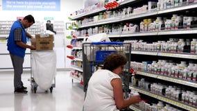 Движение людей принимая деталь чулка здоровой еды и клерка на полке на раздел фармации внутри магазина Walmart