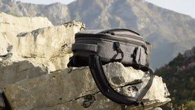 Движения камеры вдоль рюкзака на скале горы против красивого пика гор видеоматериал
