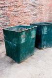 Двиньте под углом вертикальный взгляд 2 зеленых мусорной корзины снаружи против красного цвета Стоковые Изображения