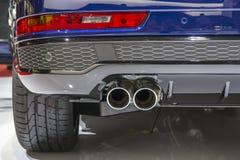 Двойная выхлопная труба хрома сильной спортивной машины с серыми пластиковыми деталями стоковое фото