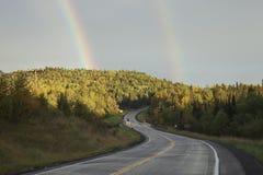 Двойная радуга над дорогой изгибая через холмы в северном Minn стоковые фотографии rf