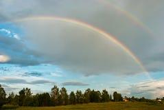 Двойная радуга над полем и домом Стоковое Изображение