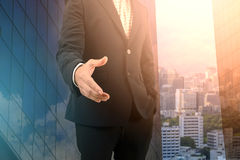 Двойная экспозиция бизнесмена давая его руку для рукопожатия с городским пейзажем Стоковое фото RF