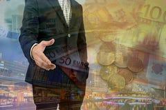 Двойная экспозиция бизнесмена давая его руку для рукопожатия с городским пейзажем и деньгами ЕВРО Стоковое фото RF