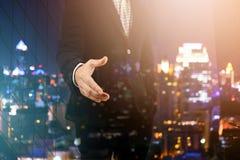 Двойная экспозиция бизнесмена давая его руку для рукопожатия с городским пейзажем Стоковые Изображения