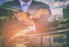 Двойная экспозиция бизнесмена в черном костюме, поднимая обе руки, предпосылка вокзал неба и городской пейзаж стоковое изображение