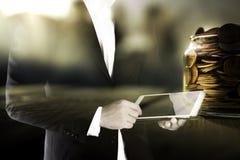 Двойная экспозиция бизнесмена используя таблетку и золотых монеток в концепции вклада опарника, технологии и банка Стоковое фото RF