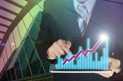 Двойная экспозиция бизнесмена используя таблетку с финансовой диаграммой Стоковые Изображения