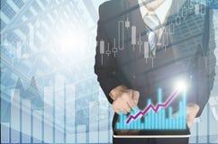 Двойная экспозиция бизнесмена используя таблетку с финансовой диаграммой Стоковое Изображение RF