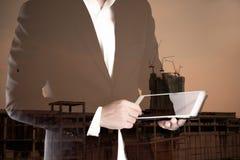 Двойная экспозиция бизнесмена используя таблетку для деятельности недвижимости Стоковые Изображения