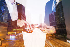 Двойная экспозиция бизнесмена и женщины используя smartphone с стоковое изображение rf