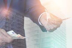 Двойная экспозиция бизнесмена с деньгами в его руках и const Стоковое Изображение RF