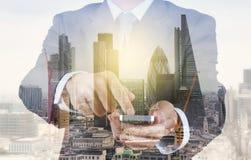 Двойная экспозиция бизнесмена успеха используя умный телефон стоковая фотография