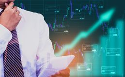 Двойная экспозиция - бизнесмен держа планшет в руке, предпосылке символ стрелки и графике состояния запасов, со значком кредитной стоковые изображения