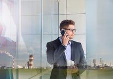 Двойная экспозиция городского привлекательного бизнесмена с телефоном devic Стоковые Изображения RF