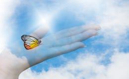 Двойная экспозиция голубого неба, облаков и бабочки сидя на руке женщины стоковые изображения rf