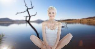 Двойная экспозиция женщины выполняя йогу на береге озера Стоковые Изображения RF