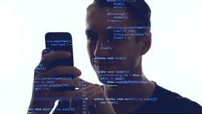 Двойная экспозиция программиста человека используя смартфон с голубым кодом на ем Приложение разработки концепции для смартфона сток-видео