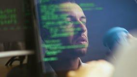 Двойная экспозиция снятая программиста хакера человека работая на ноутбуке Отражение в мониторе: Разработчик пишет зеленый код видеоматериал
