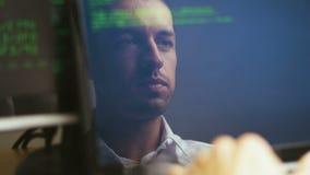 Двойная экспозиция снятая программиста хакера человека работая на ноутбуке Отражение в мониторе: Разработчик пишет зеленый код сток-видео