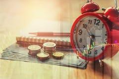 двойная экспозиция стога и диаграммы монеток с красным будильником fo Стоковые Изображения