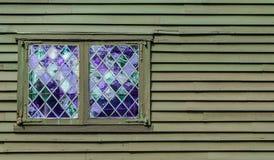 Двойное окно с фиолетовыми форточками в ромбовидном узоре в стене колониального здания Стоковая Фотография RF