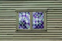 Двойное окно с фиолетовыми форточками в ромбовидном узоре в стене колониального здания Стоковая Фотография