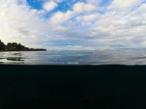 Двойной ландшафт с морем и небом Над и под водораздел в тропическом seashore Темная морская вода и солнечное небо Стоковые Изображения RF