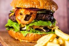 Двойной бургер на доске на деревянной предпосылке Стоковое фото RF