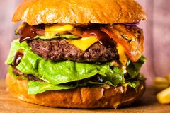 Двойной бургер на доске на деревянной предпосылке Стоковая Фотография