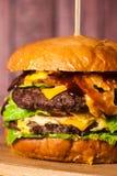 Двойной бургер на доске на деревянной предпосылке Стоковое Изображение RF