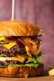 Двойной бургер на доске на деревянной предпосылке Стоковые Изображения RF