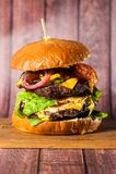 Двойной бургер на доске на деревянной предпосылке Стоковые Фотографии RF